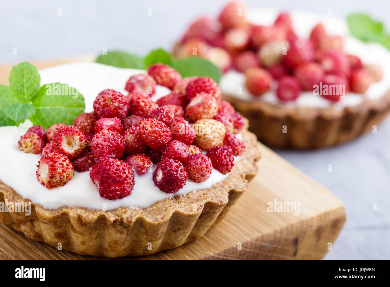 Wild strawberry tartlets with cream filling, delicious summer fruit mini tarts on rustic cutting board - Stock Image