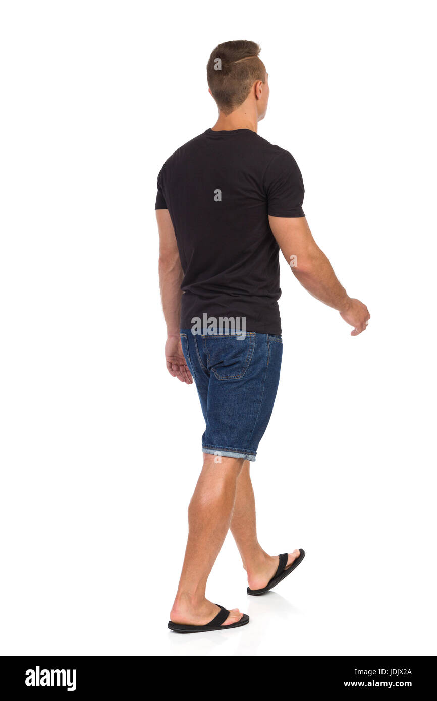 Young man walking in black shirt, jeans shorts and black flip-flops. Rear side view. Full length studio shot isolated - Stock Image