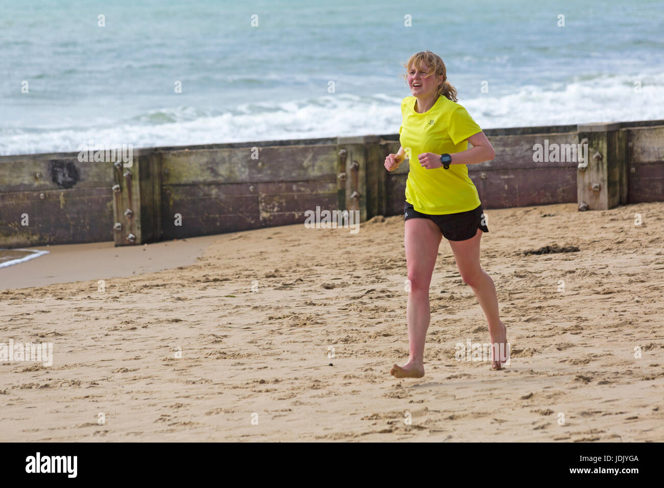 Young woman running bare footed along seashore at Bournemouth beach at Bournemouth, Dorset in April Stock Photo