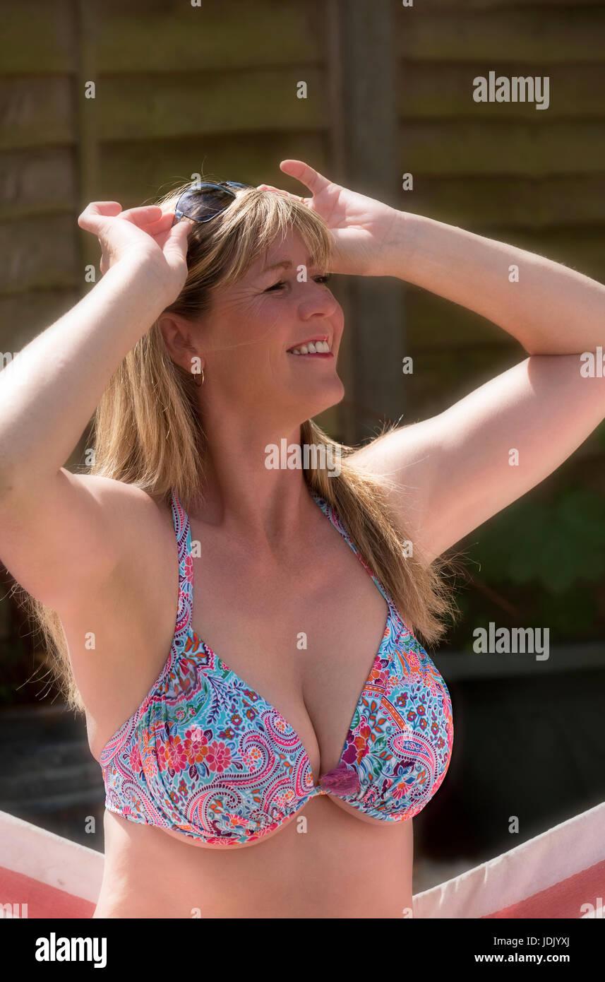 Woman wearing a bikini top annd holding sun glasses in her hair - Stock Image