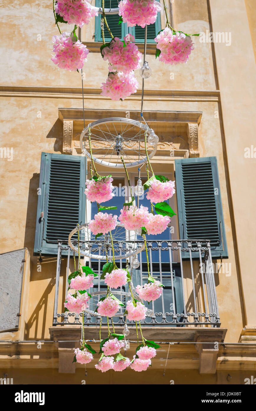 Alghero old town, a festive display of pink flowers and bicycle wheels suspended above the Piazza Civica in the - Stock Image