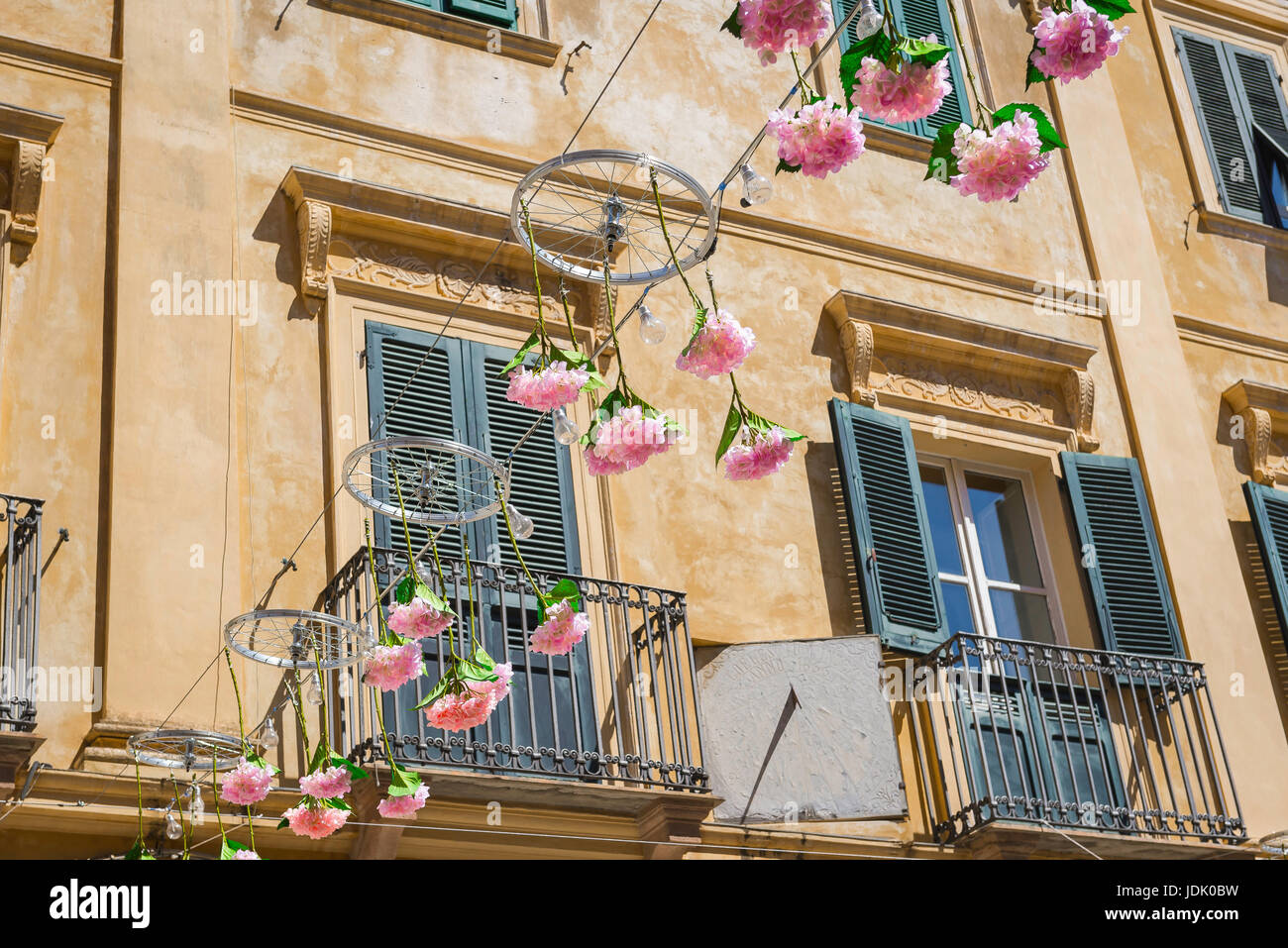 Alghero Sardinia old town, a festive display of pink flowers and bicycle wheels suspended above the Piazza Civica - Stock Image