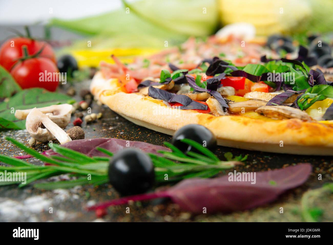 Italian pizza with mozzarella, black olives, prosciutto and tomatoes Stock Photo