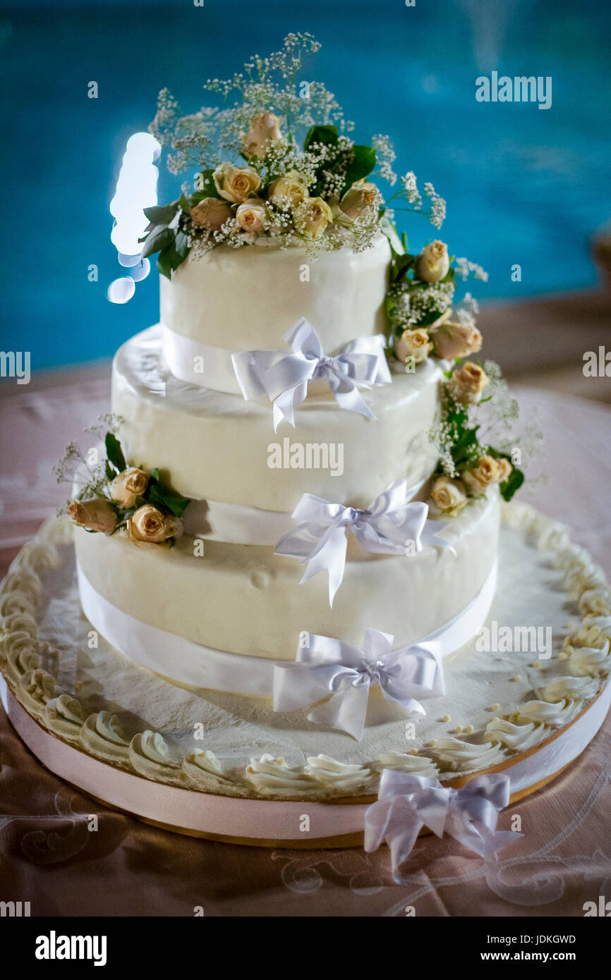 three-tiered withe wedding cake  with yellow roses - Stock Image