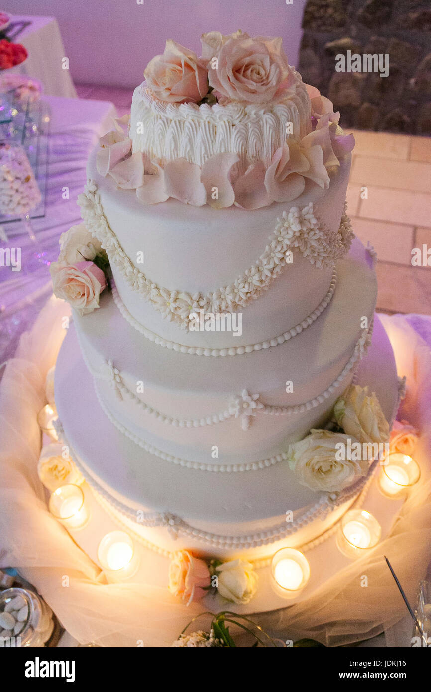 wedding cake with candls and pink roses - Stock Image