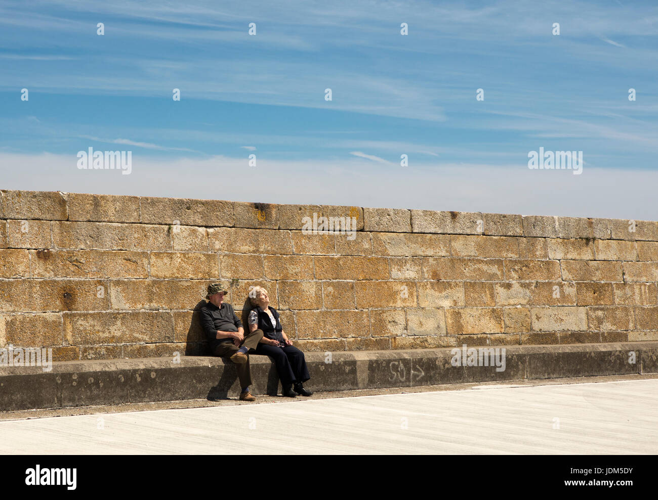 Howth, Ireland. 21st June, 2017. A man and woman snooze in the sun on Howth Pier on a hot summer day in Co. Dublin, - Stock Image