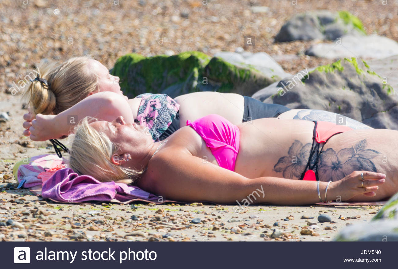 A couple of women with tattoos and wearing bikinis laying on the beach sunbathing in Summer in the UK. - Stock Image