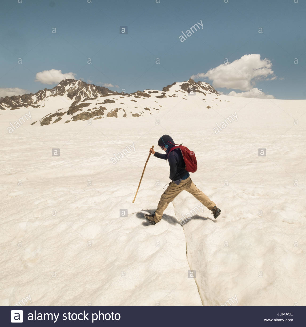 A European boy jumps over a small crevasse on a glacier in the mountains. - Stock Image
