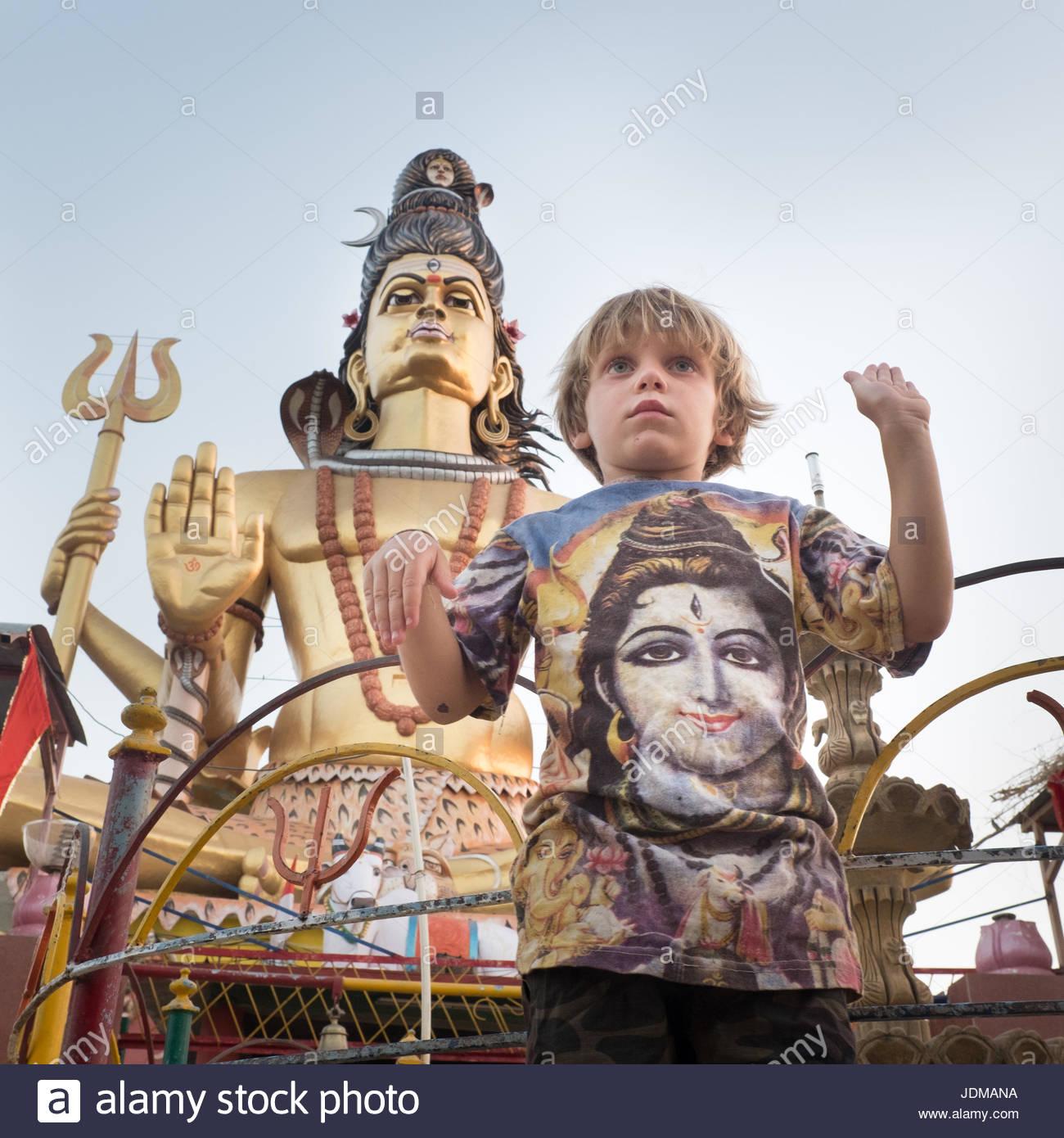 A European boy tries to imitate the pose of Shiva. - Stock Image