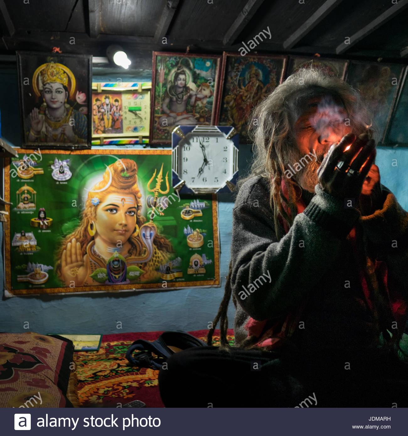 A Sadhu smoking marijuana in his home in the Himalayas. - Stock Image