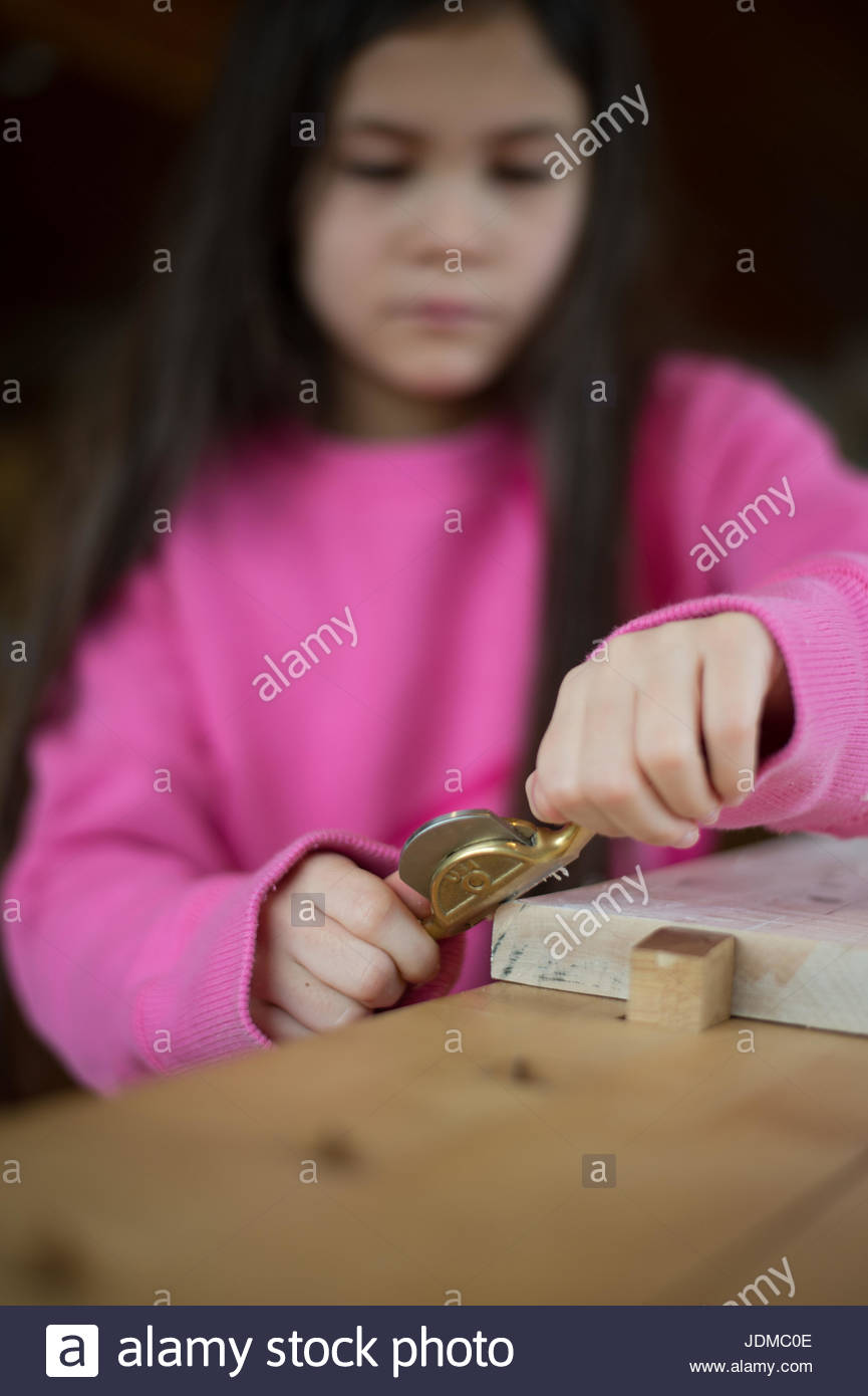 A young girl uses a woodworking tool at a tool factory. - Stock Image