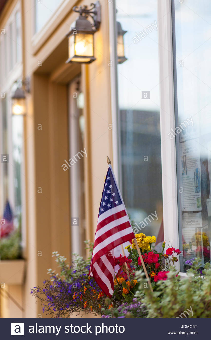 An American flag in a flower box. - Stock Image