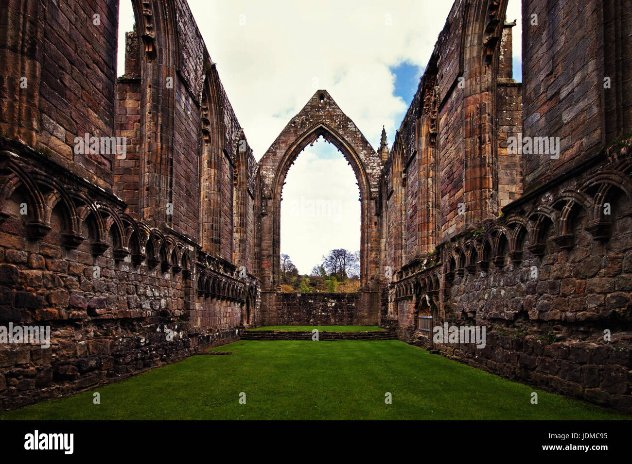 The lawned ruins in the central section of Bolton Abbey - Stock Image