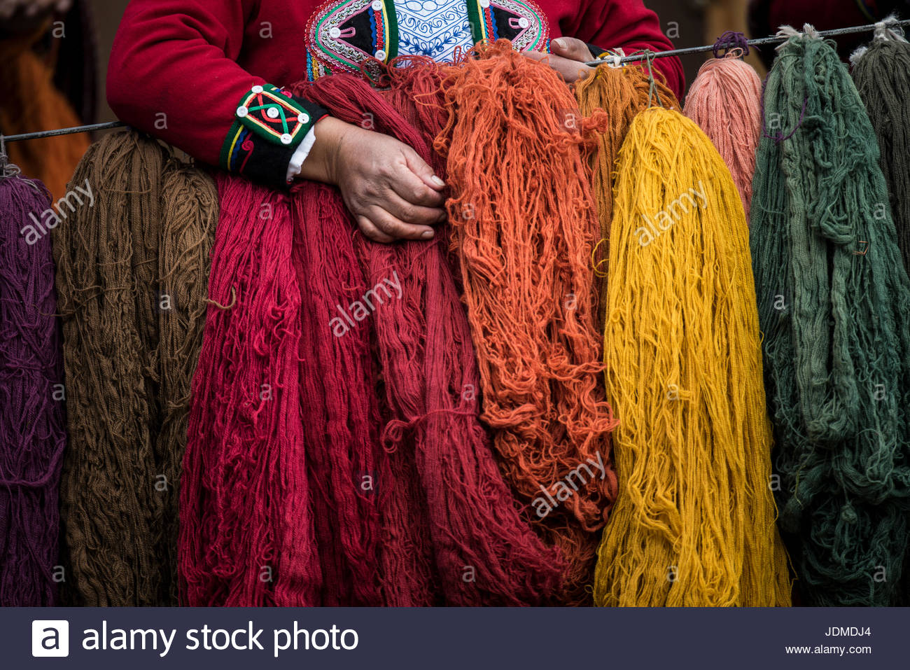 Quechuan women of Chinchero weave traditional clothes in traditional ways for sale. - Stock Image