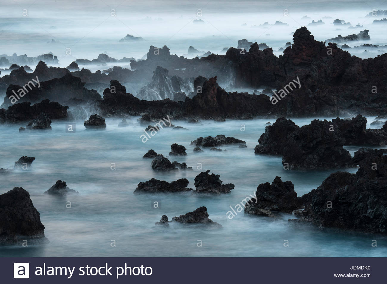 A long exposure of surf pouring over lava rocks at Easter Island. - Stock Image