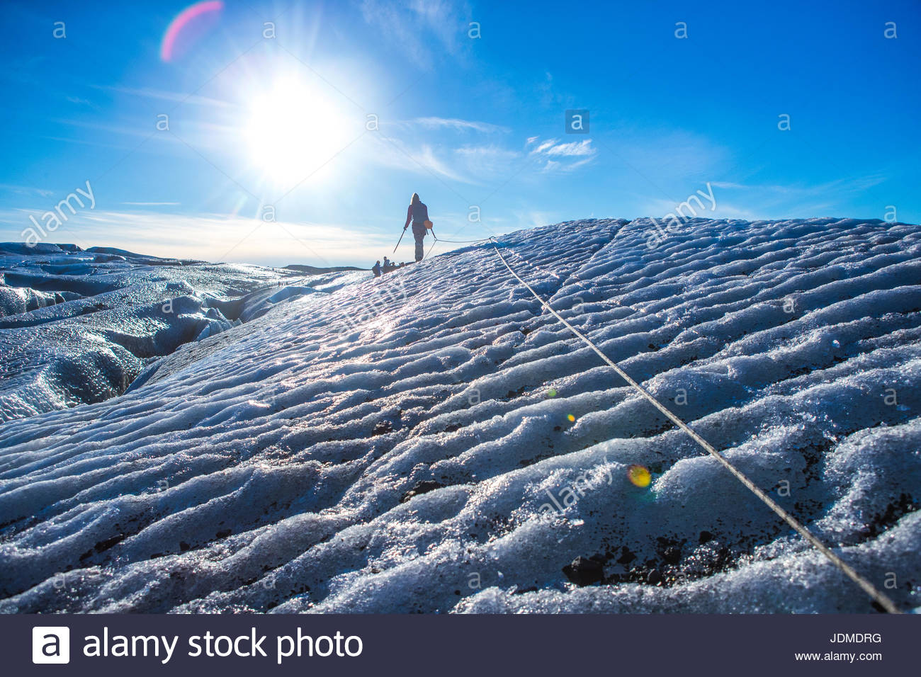 A woman walks along a safety rope to keep from sliding into a crevasse on the Vatnajokull Glacier. - Stock Image