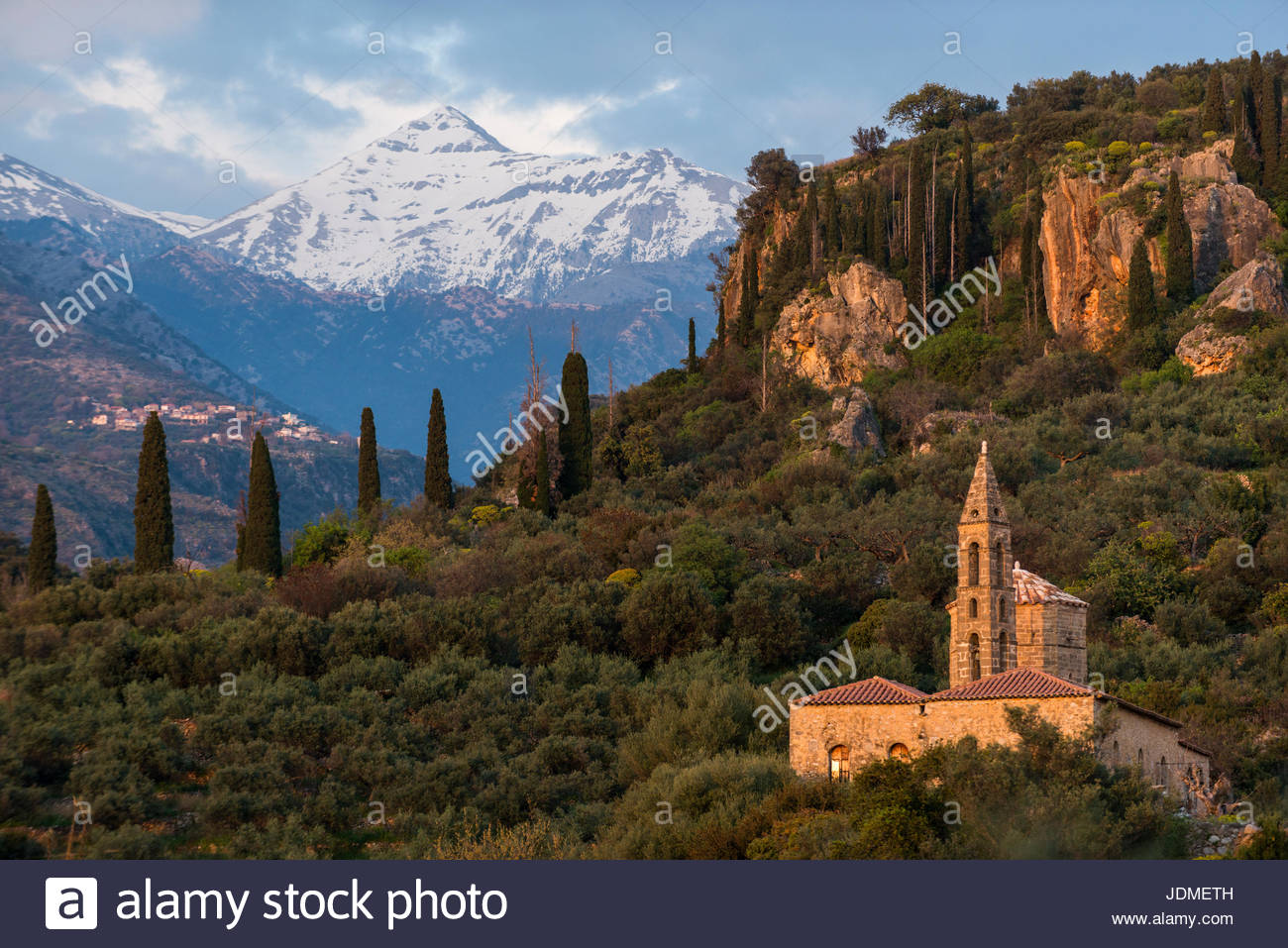 The Taygetos mountains loom behind a church in the Peloponnese. - Stock Image