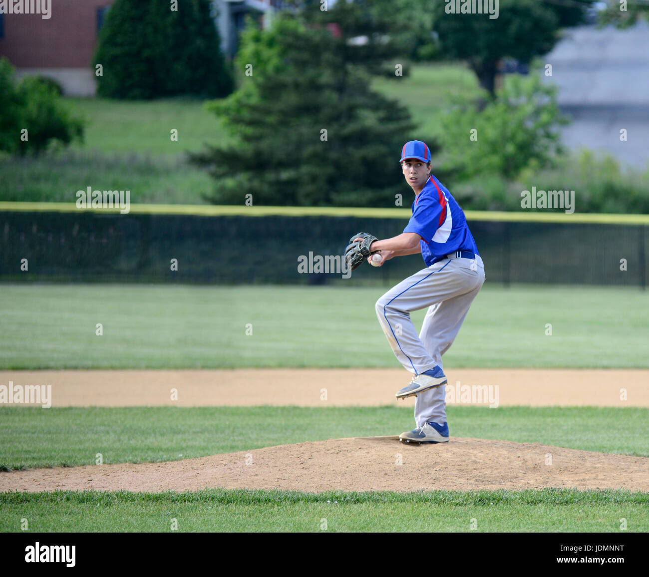 teenage boy winding up and ready to throw a baseball on the pitching mound - Stock Image