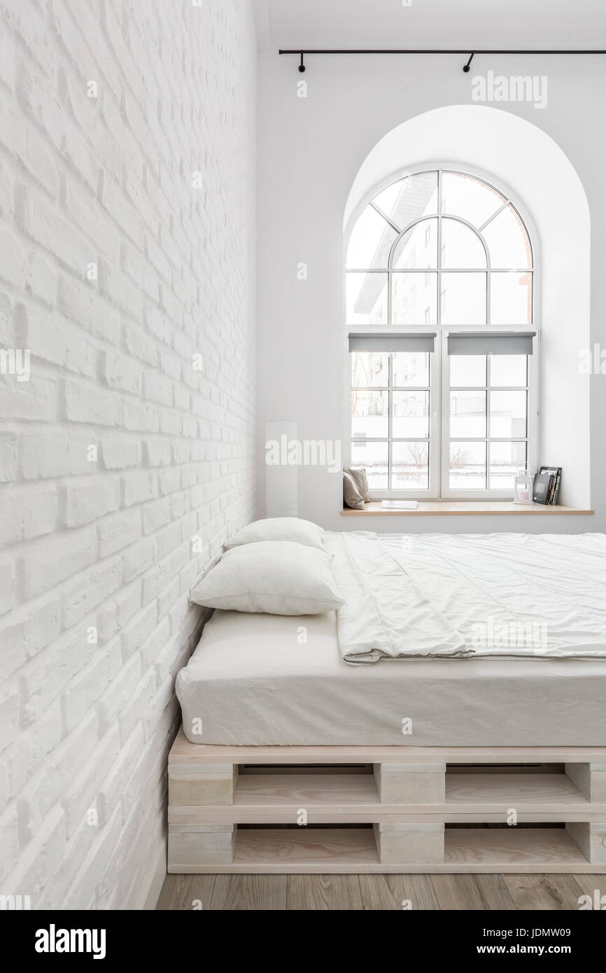 half circle window shutters white bedroom with double bed brick wall and half circle window