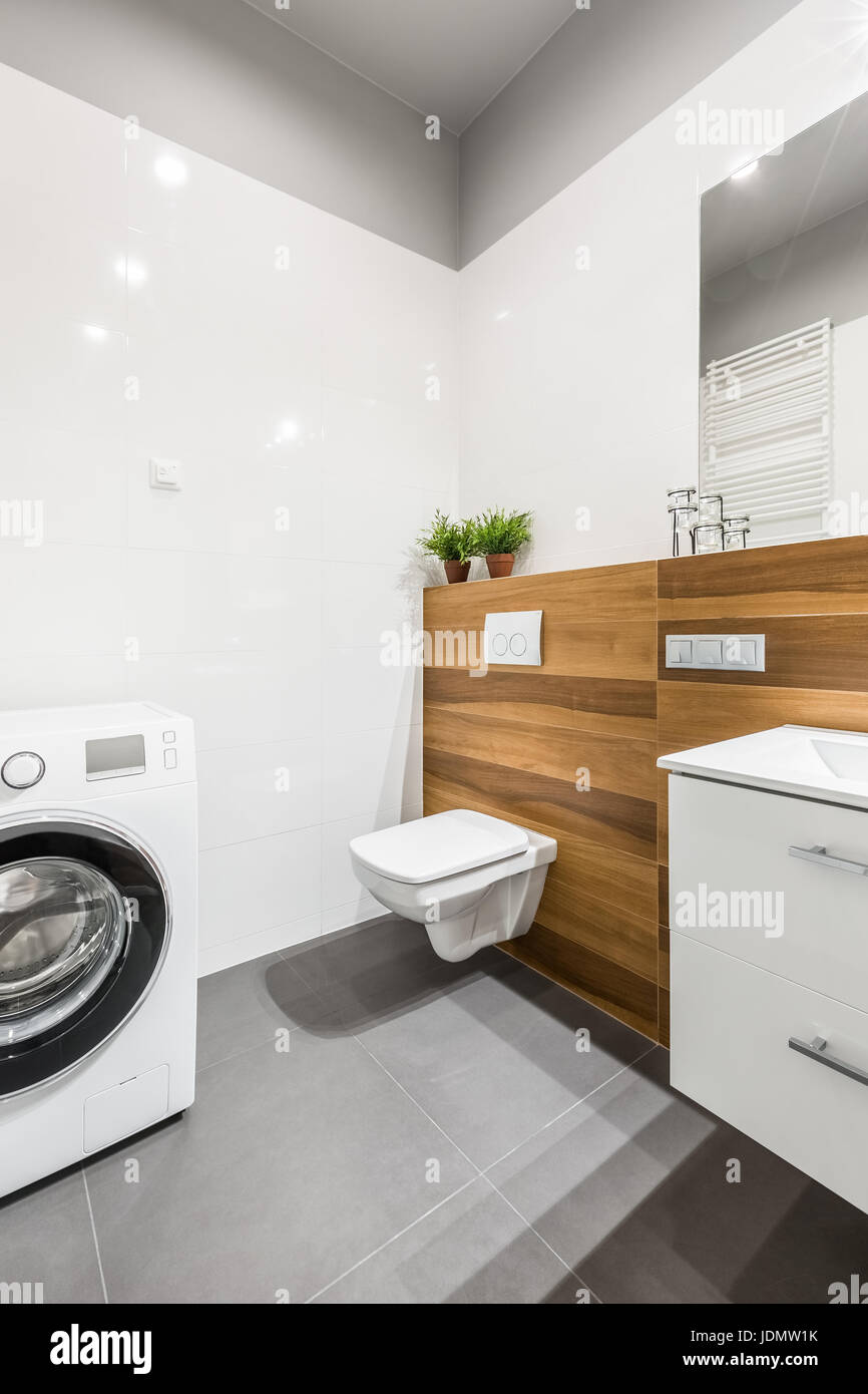 Modern, gray and white bathroom with washing machine, toilet and ...