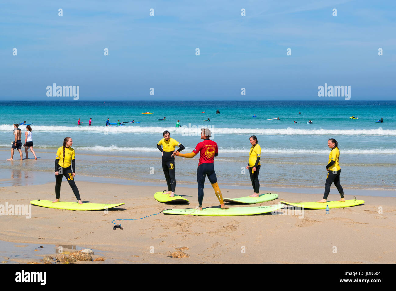 surfing lessons on the beach at sennen cove in cornwall, england, uk. - Stock Image