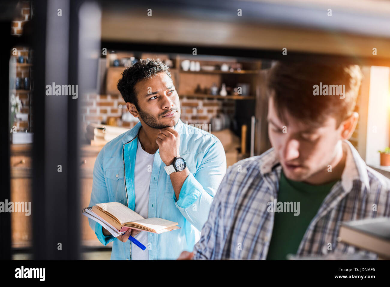young professional group working with books in small business office - Stock Image