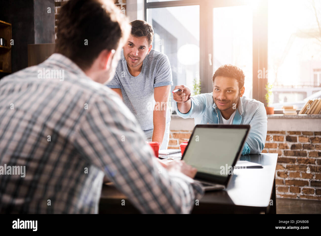 Young man using laptop while colleagues discussing project, small business meeting concept - Stock Image