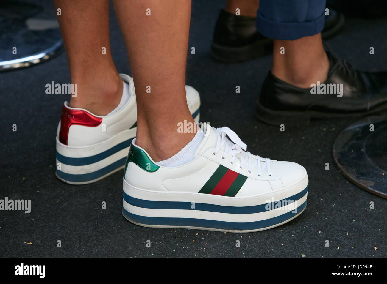 18c06bd65c3 MILAN - JUNE 19  Man with white Gucci wedge heel sneakers shoes before  Fendi fashion show
