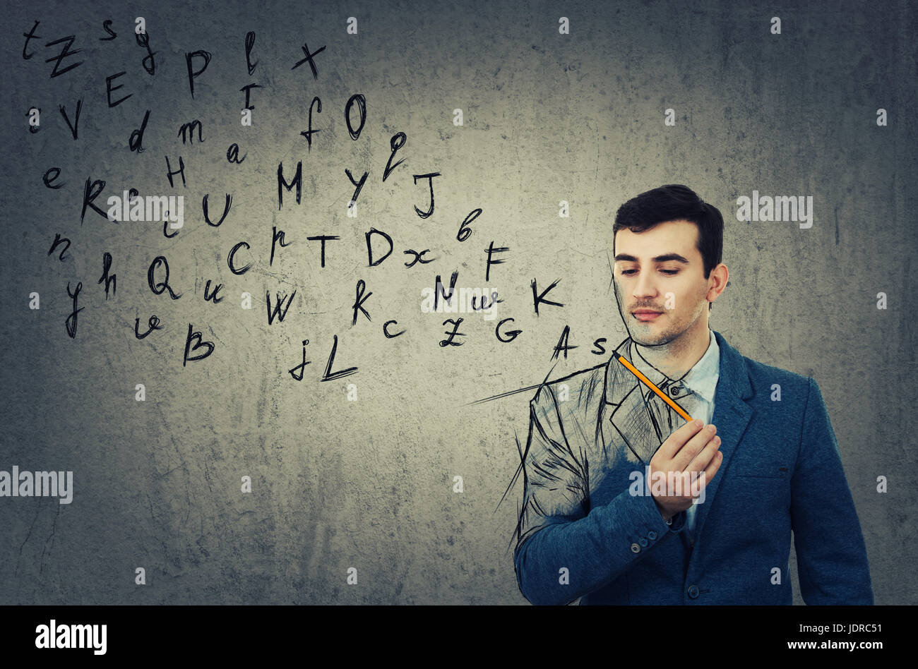 Young businessman holding a pencil in his hand  and looking at the sketched alphabet letters coming out. Education - Stock Image