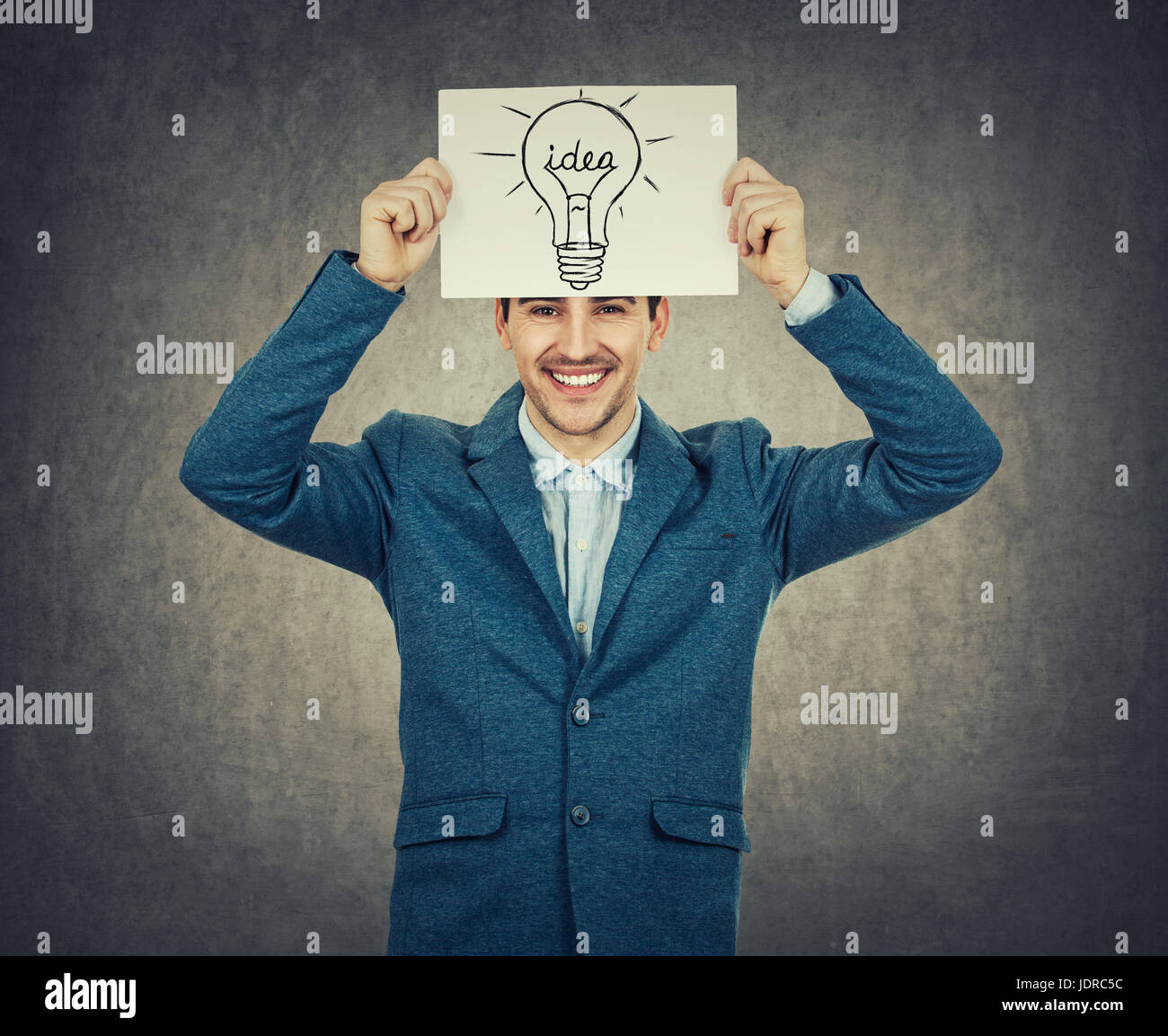 Smiling businessman or teacher holding a white paper above his head with a light bulb sketch. Science and business - Stock Image