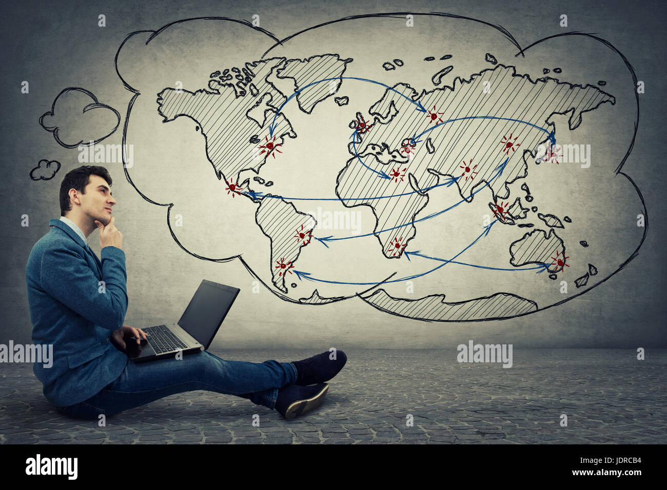 Young serious businessman sitting down on floor using laptop, thinking about global network and globalization concept. - Stock Image