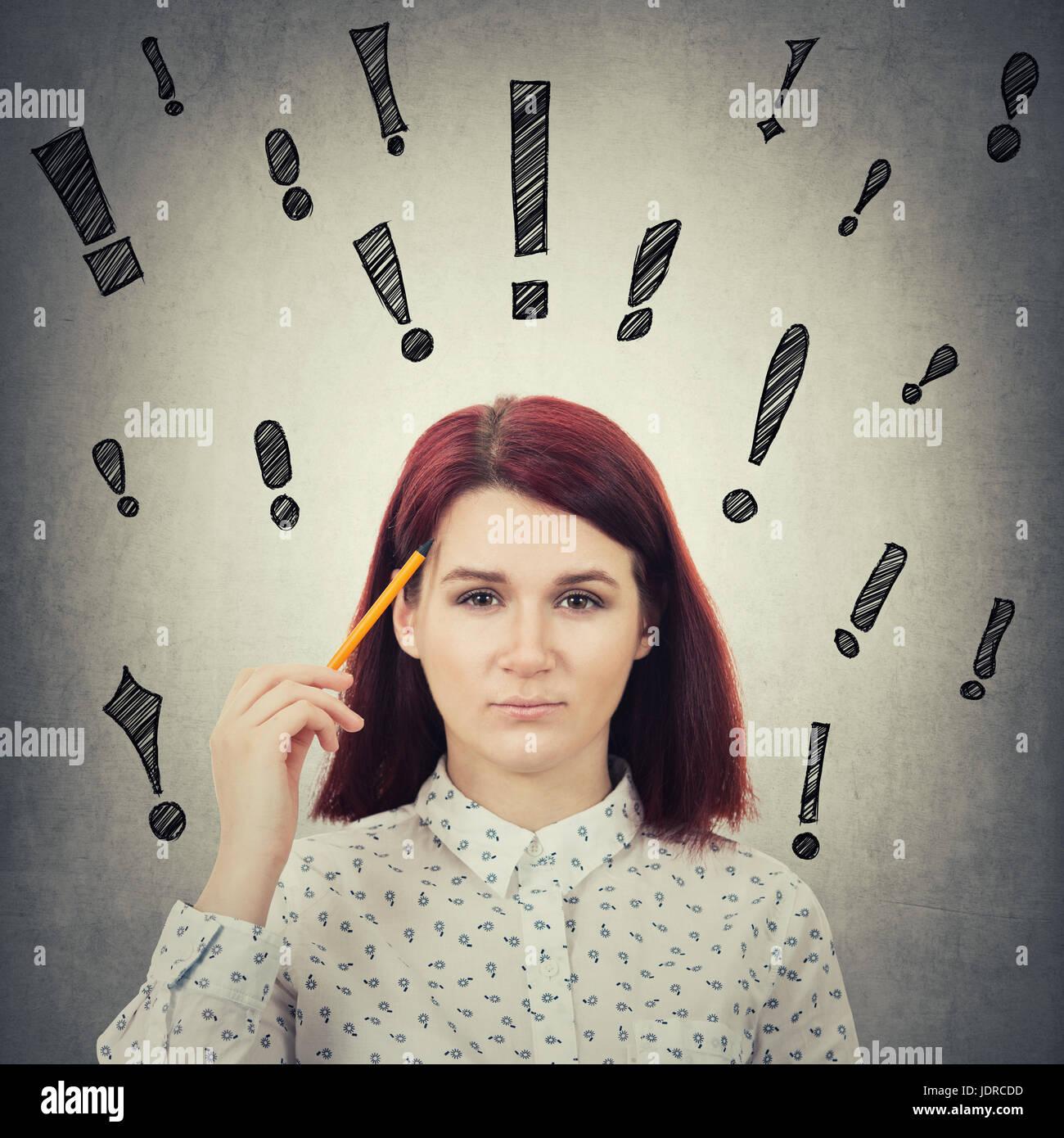Serious businesswoman holding a pencil pointed to face, drawing different exclamation marks like different thoughts - Stock Image