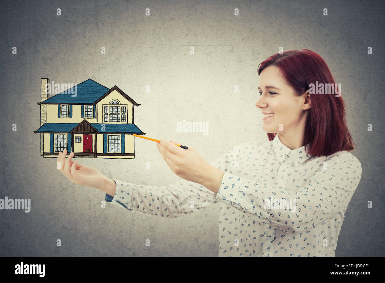 Young smiling girl drawing a family house in her hand. Home protection and proprety insurance concept isolated on - Stock Image