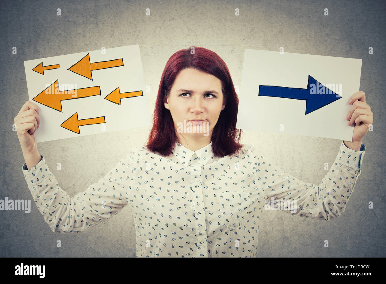 Confused young woman holding two papers in her hands with arrows poinded to the left and right side. Human emotion, - Stock Image
