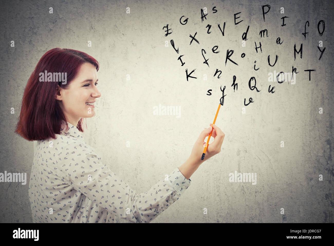 Young businesswoman, holding a pencil in her hand, drawing alphabet letters. Education and communication concept - Stock Image