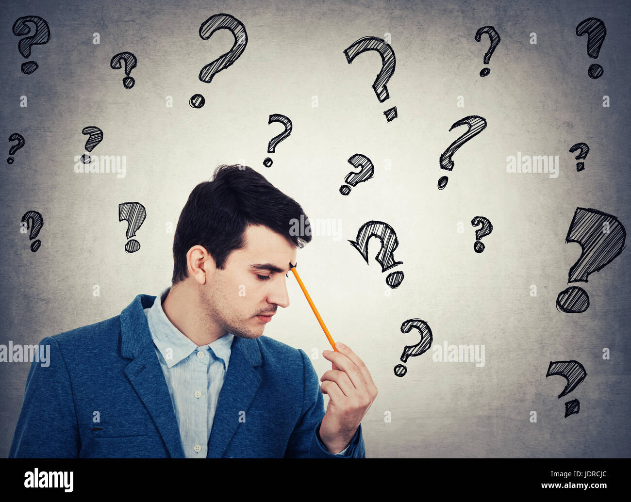 Thoughtful businessman holding a pencil pointed to face, drawing different interrogation marks like questions escaping - Stock Image