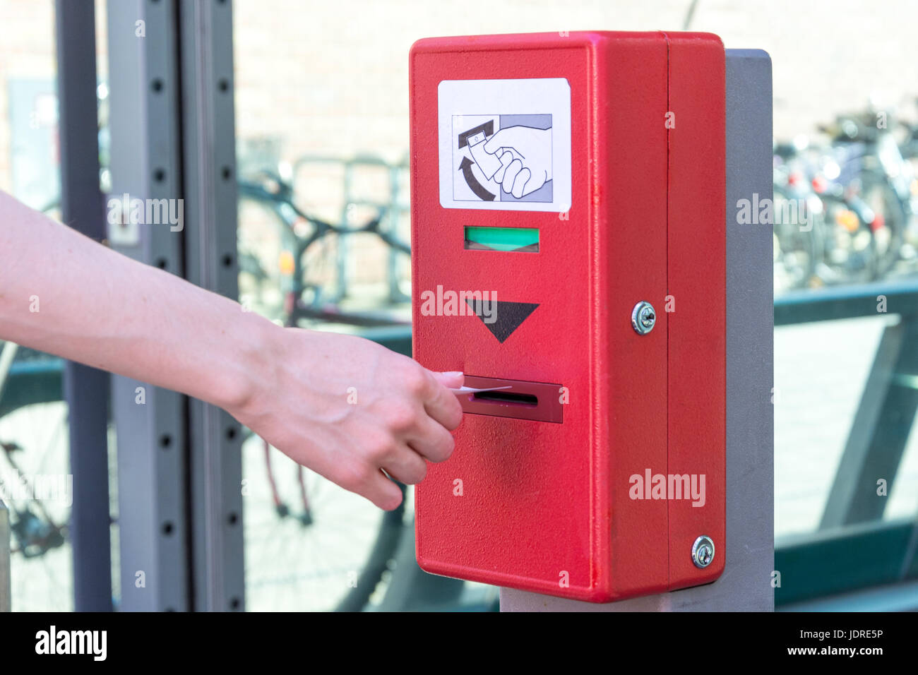 Validate a ticket at a red ticket validation machine for the underground from the side - Stock Image
