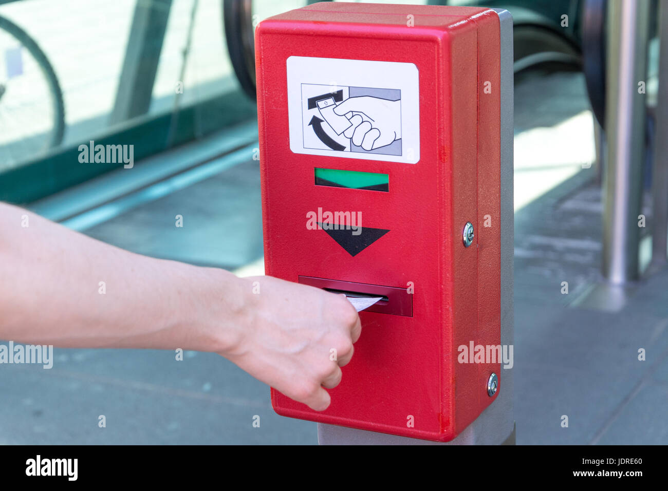 Validate a ticket at a red ticket validation machine for the underground from the side Stock Photo