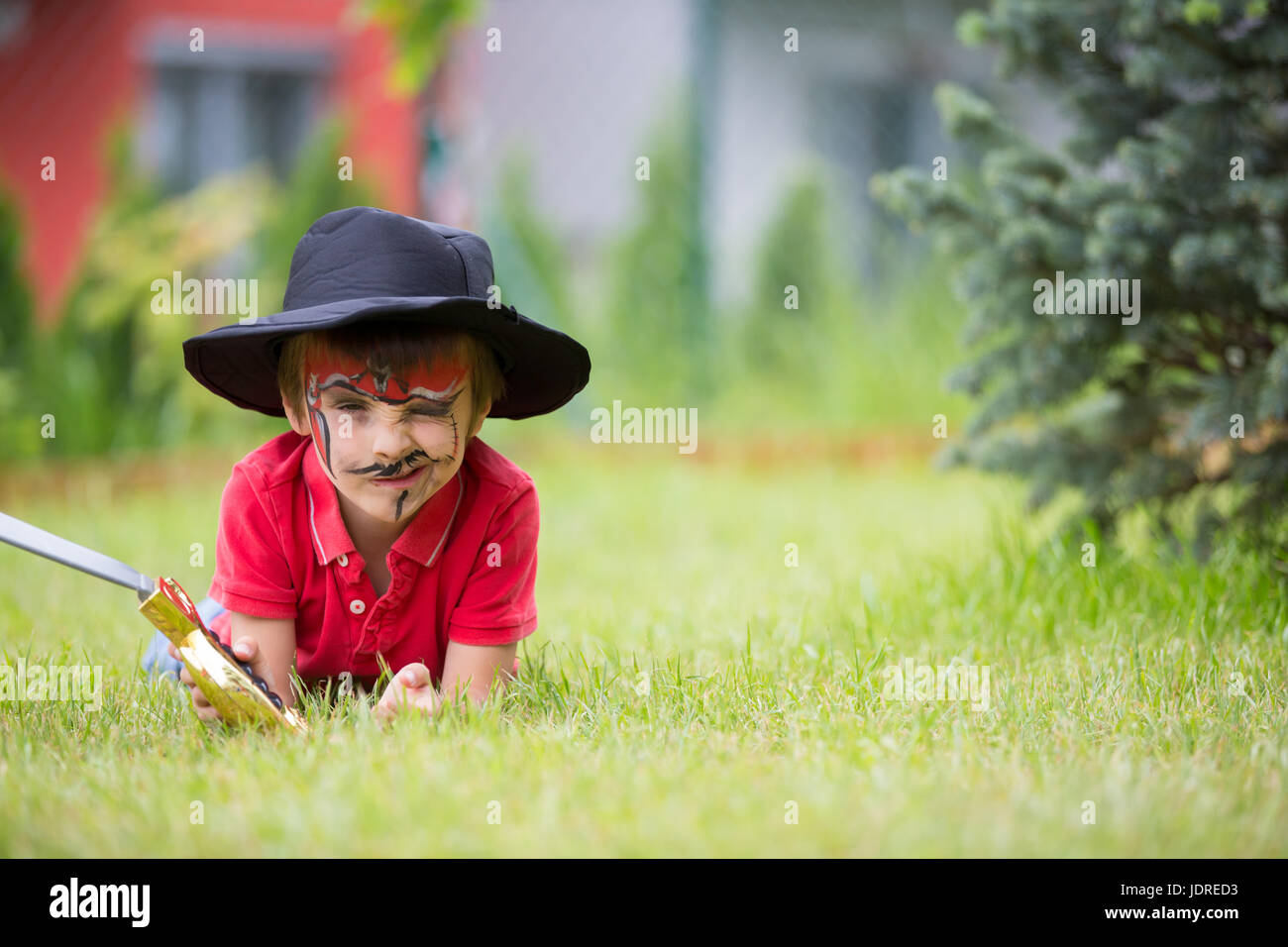 Cute school boy, playing games, painted as pirate, holding sword, play in garden, outdoor summertime Stock Photo