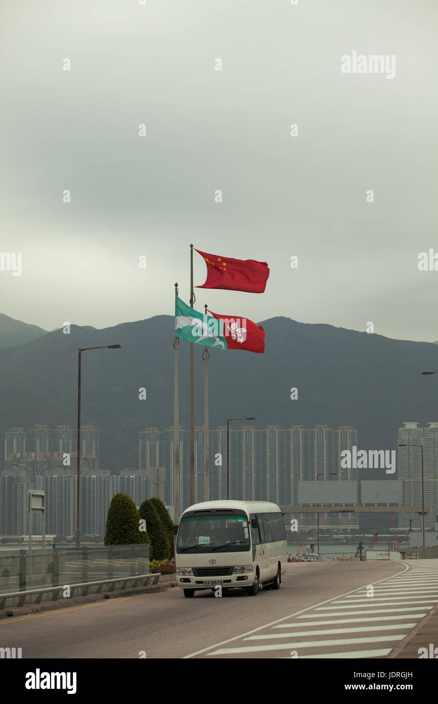 Chinese state flag with Hong Kong SAR flag at Hong Kong international airport; Shuttle bus arriving at departure - Stock Image