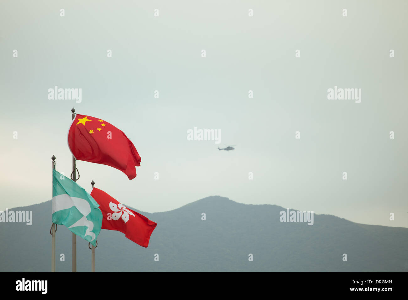 Chinese state flag with Hong Kong SAR flag at Hong Kong international airport with helicopter flying in background - Stock Image