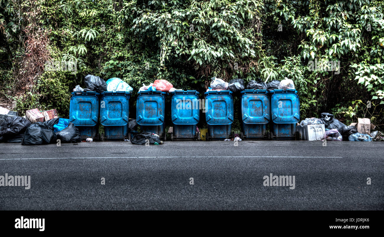 A Row of Garbage Cans Lined Overflowing at the Side of the Road - Stock Image