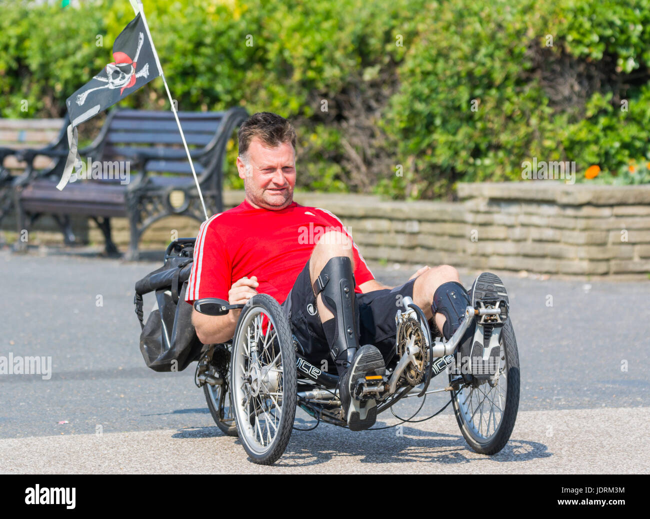 Man riding a recumbent bike along a seafront promenade on a hot day. - Stock Image