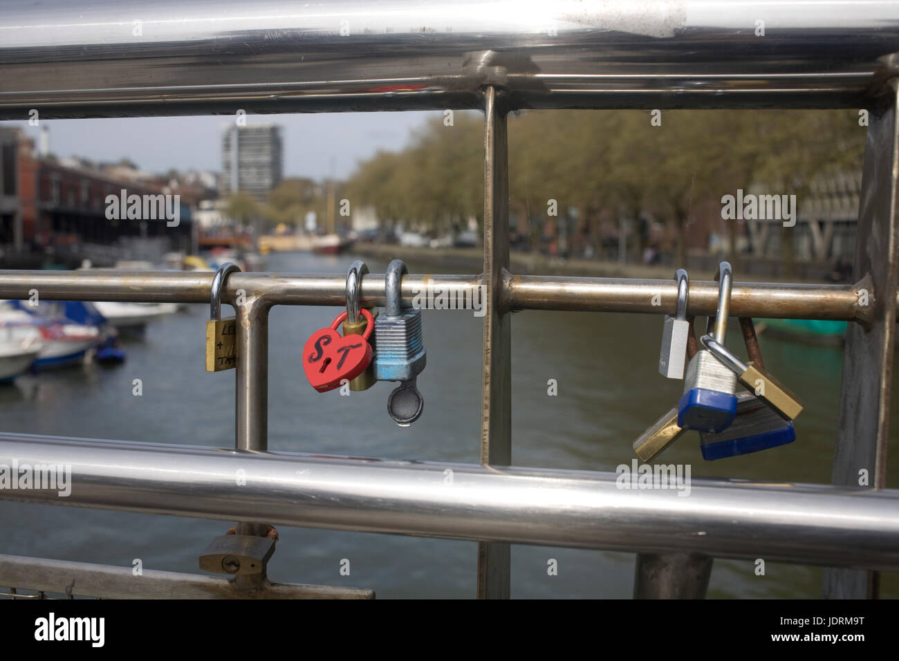 Footbridge in Bristol harbour with padlocks chained to metal railings as lovers' symbols - Stock Image