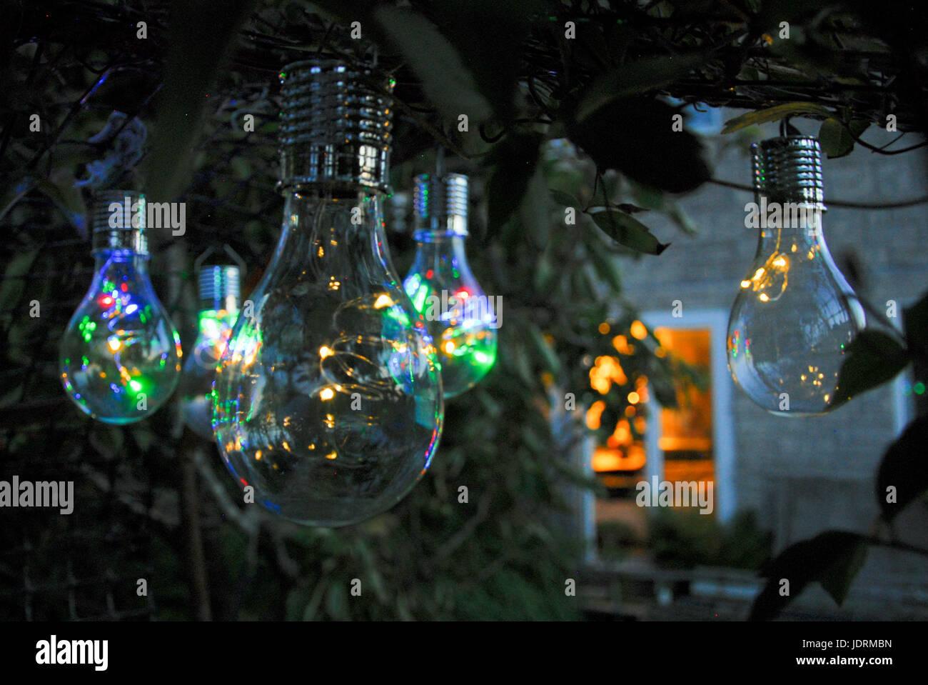 Solar-powered garden lanterns light up as night falls on the Isle of Portland - Stock Image