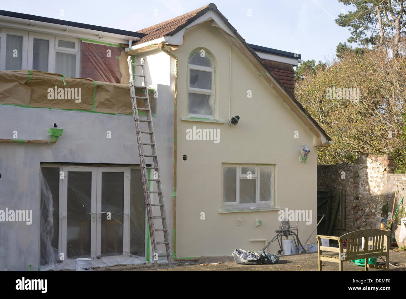 Rear of detached house during extensive repainting with special long lasting wall coating - Stock Image