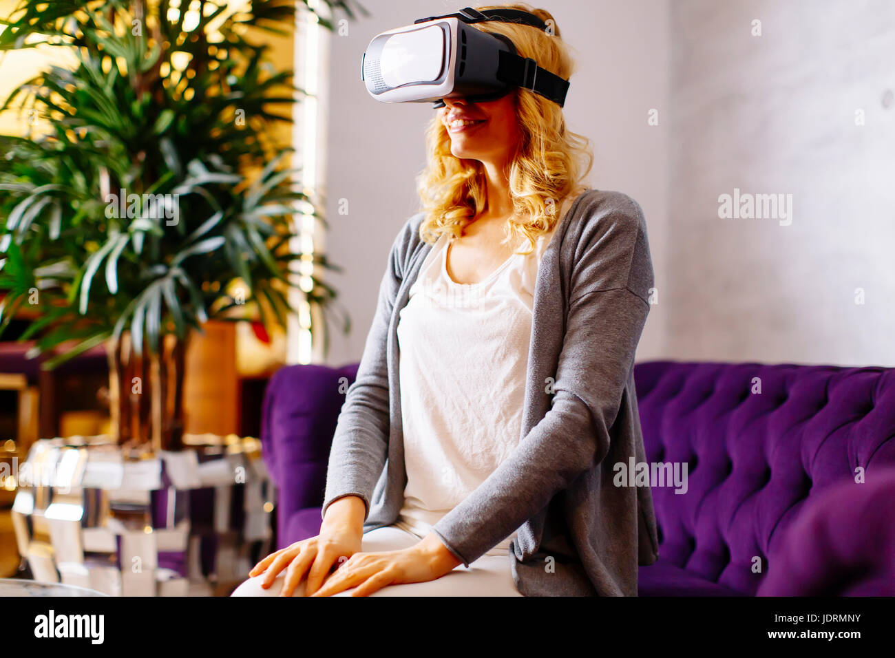 Attractive blond woman wearing headset  virtual reality vision goggles and watching video - Stock Image