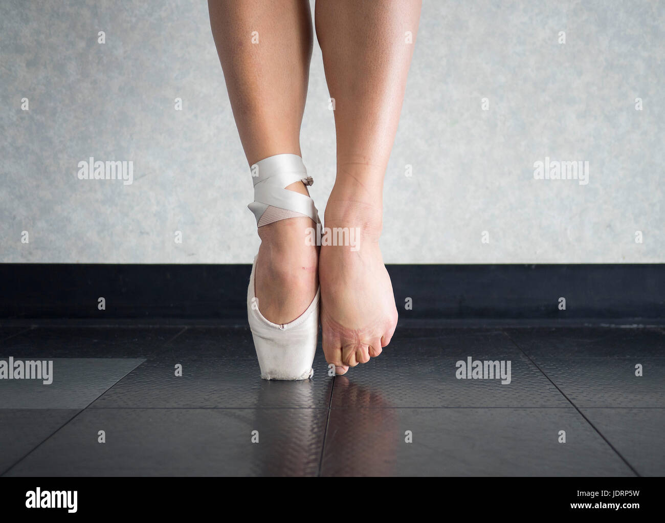 The ballet dancer balance on their pointe shoes, and the feet behind them - Stock Image