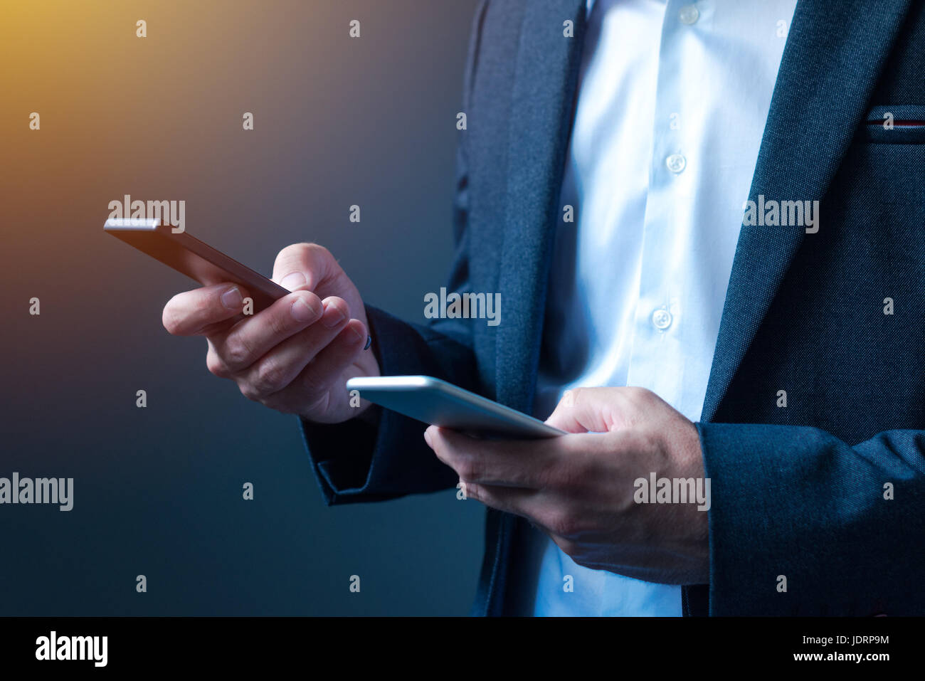 Sync and backup data on two mobile phones, man in business suit synchronizes files, messages and contact information - Stock Image