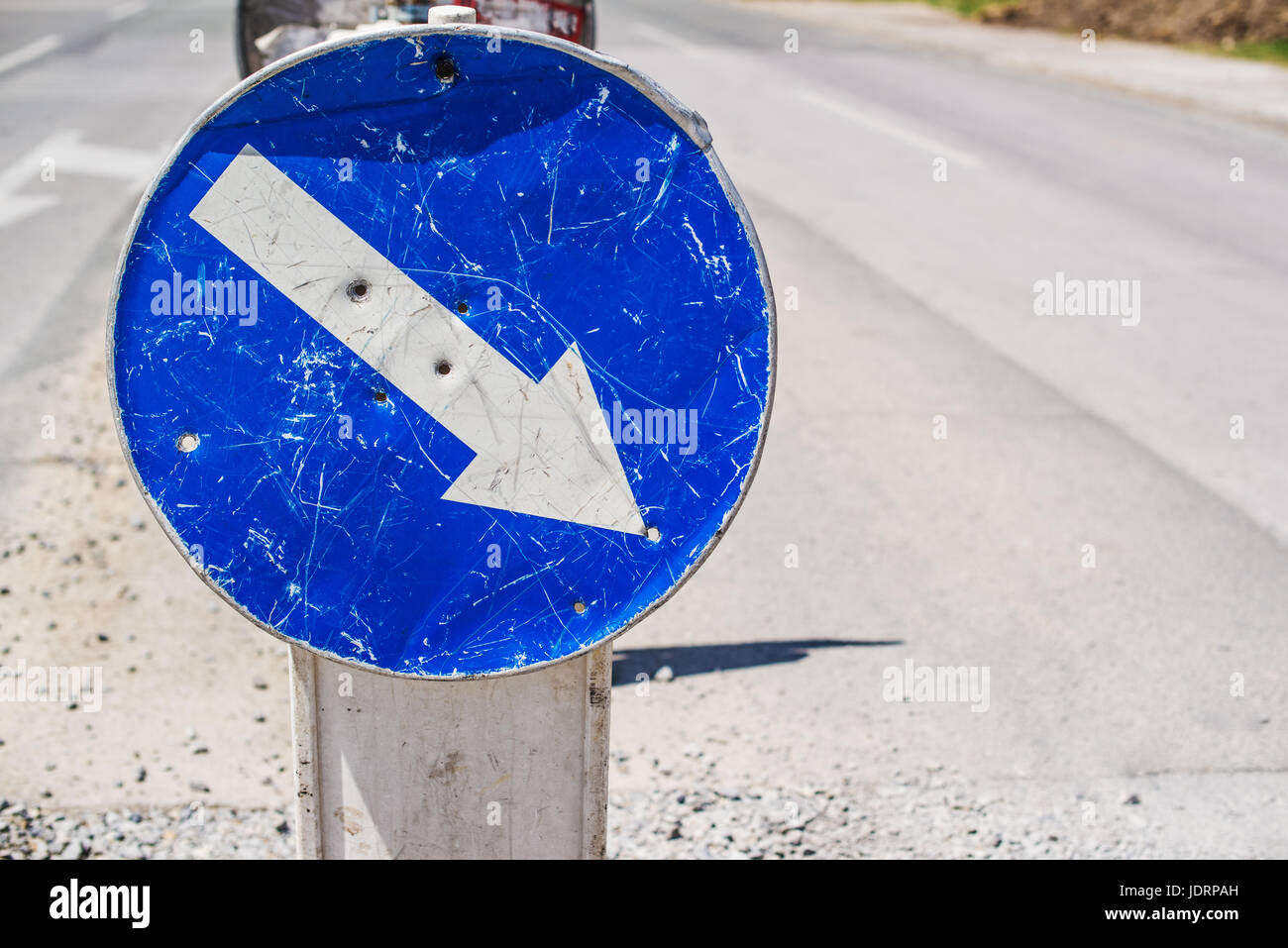 Weathered mandatory traffic direction sign on the street - Stock Image